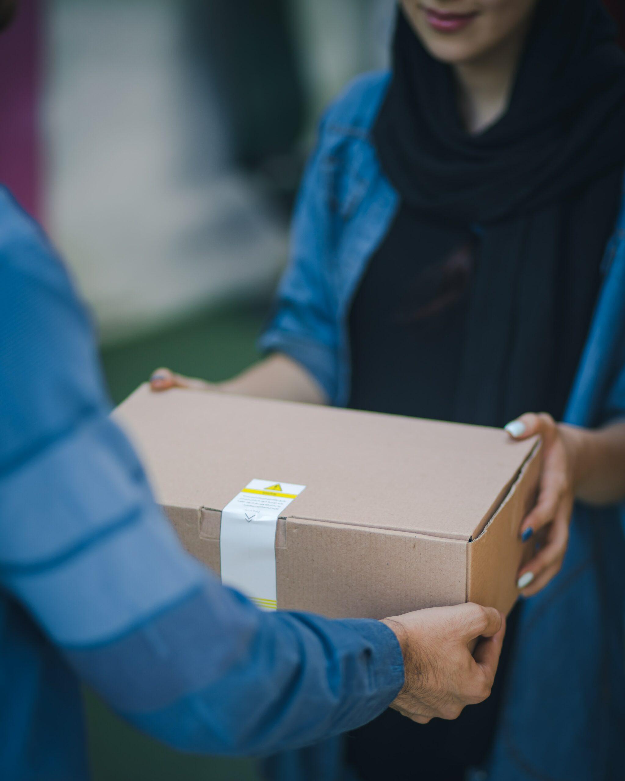 A woman handing a person a cardboard box