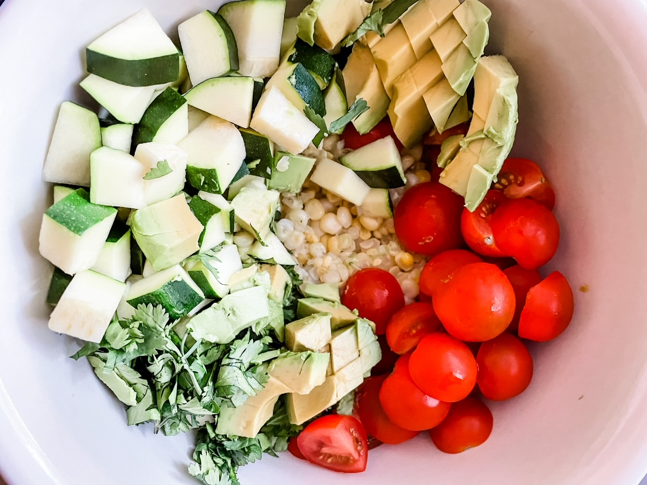 The Corn and Zucchini Salad with Avocado Dressing in a white bowl for serving