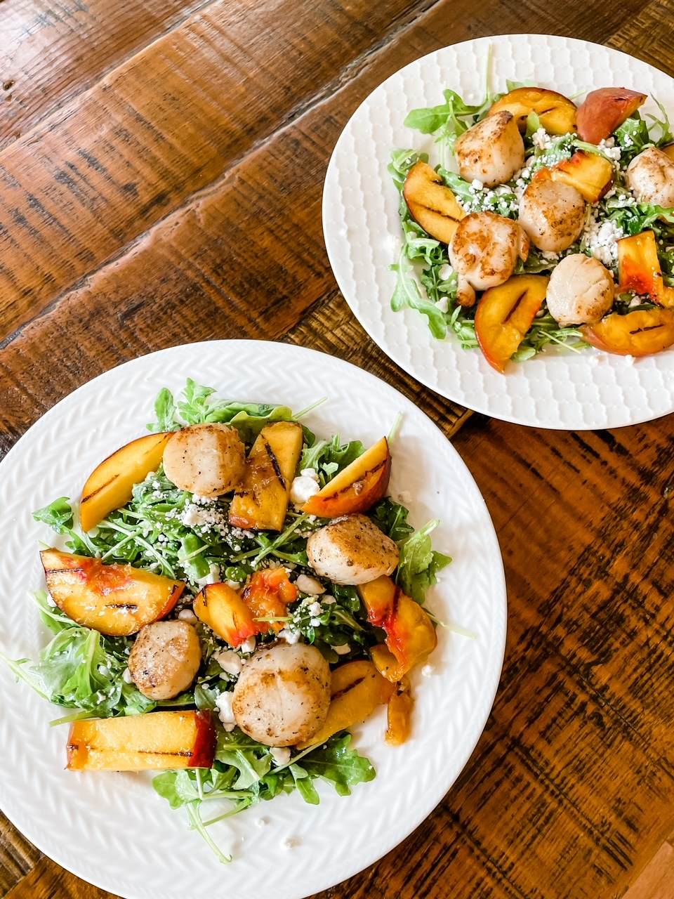 Two plates filled with the Arugula Salad with Scallops and Grilled Peaches
