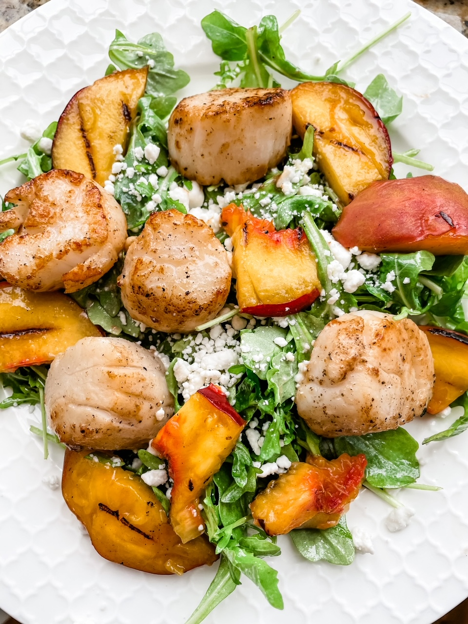 A cllose-up shot of the Arugula Salad with Scallops and Grilled Peaches