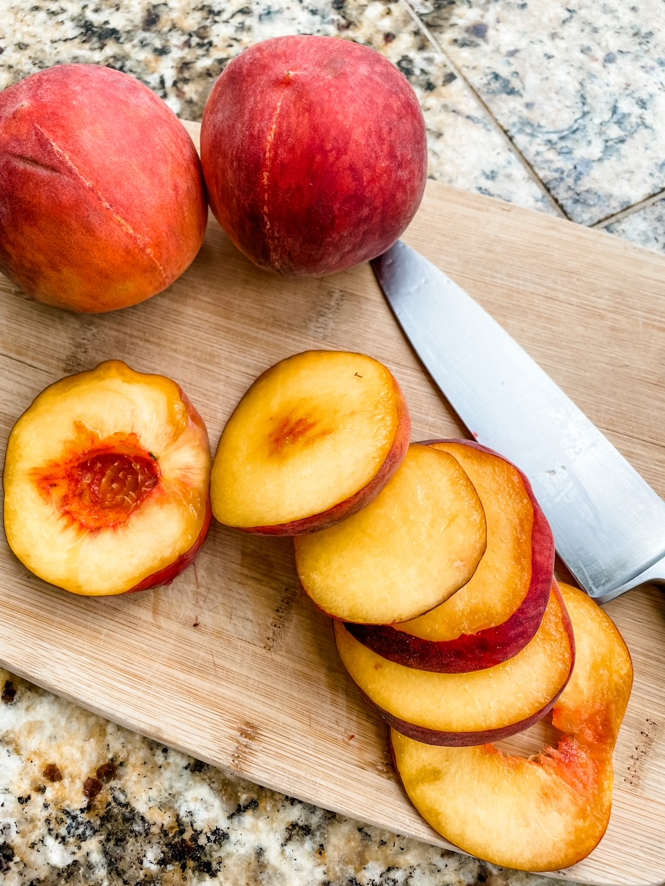 Two whole peaches and a sliced one on a cutting board