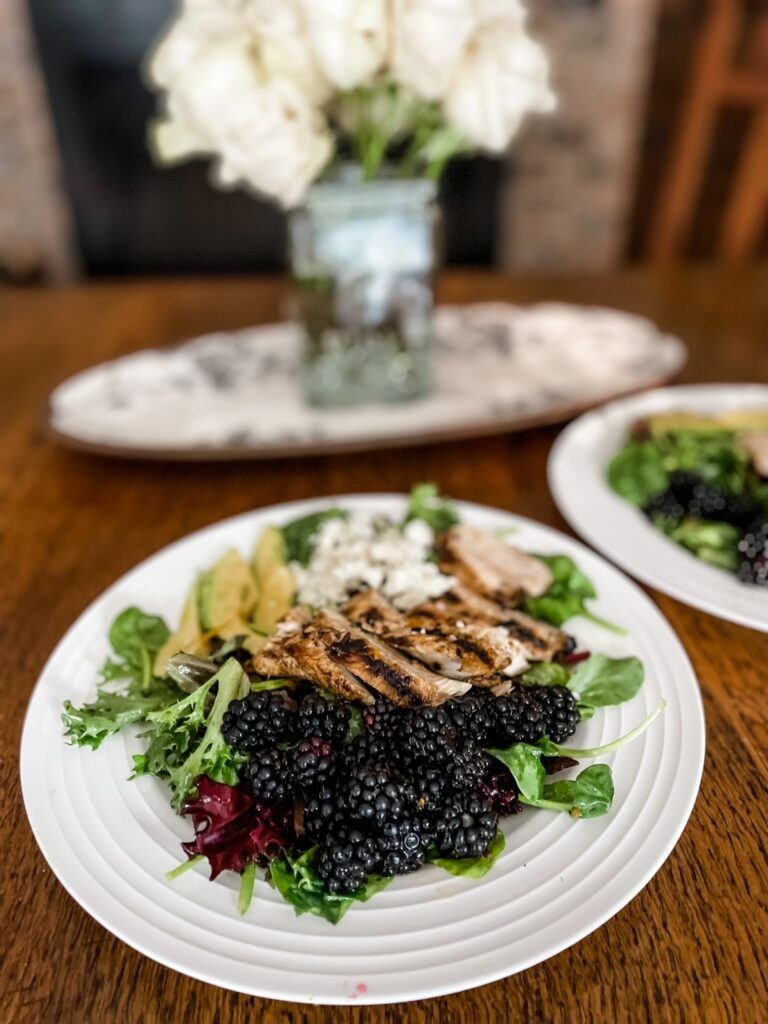 A dining table set with flowers and two plates of Marie's Blackberry and Grilled Rosemary Chicken Salad
