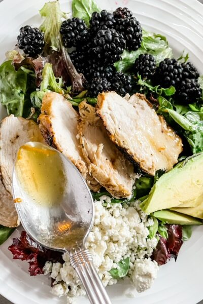 A white plate filled with the Blackberry and Grilled Rosemary Chicken Salad and a spoon above drizzling extra vinaigrette on top