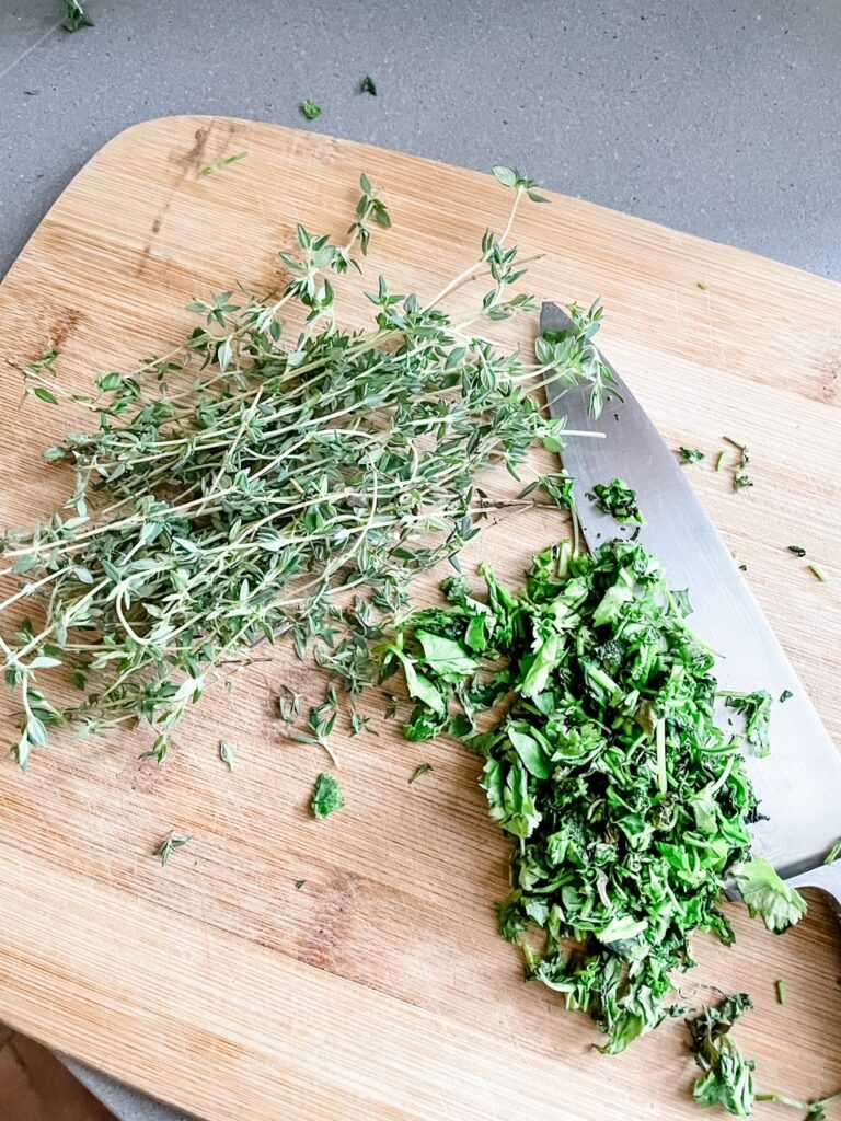 Thyme and cilantro being chopped on a cutting board