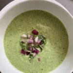 A bowl of the Cold Cucumber Soup garnished with chopped red onions