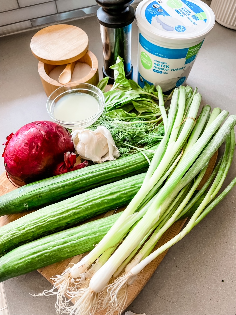 The ingredients for the Cold Cucumber Soup laid out on a countertop - cucumbers, green onion, greek yogurt, red onion, salt, and pepper