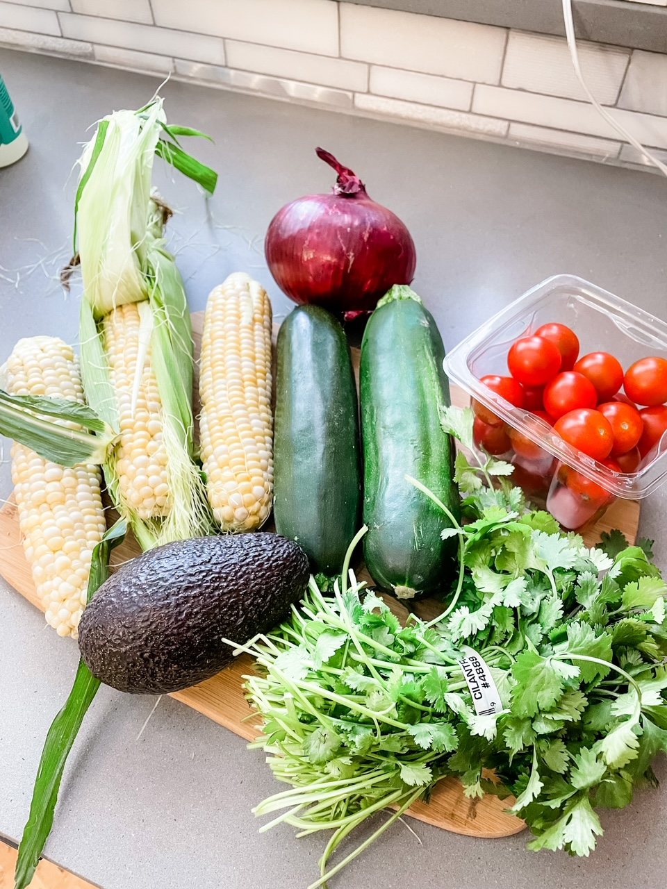 Corn, an avocado, cherry tomatoes, cucmbers, onions, and herbs on a wooden cutting tray