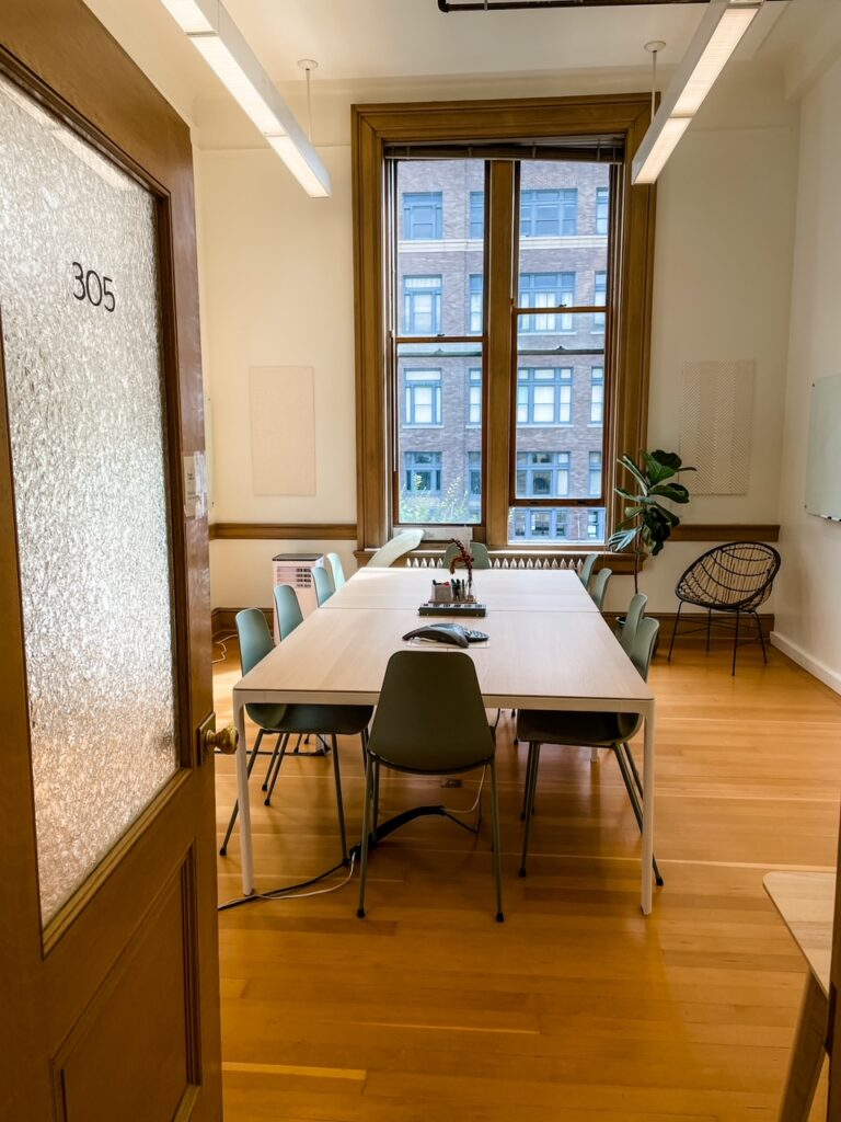 A conference room space with a long table and several chairs - a pro of the coworking space pros and cons