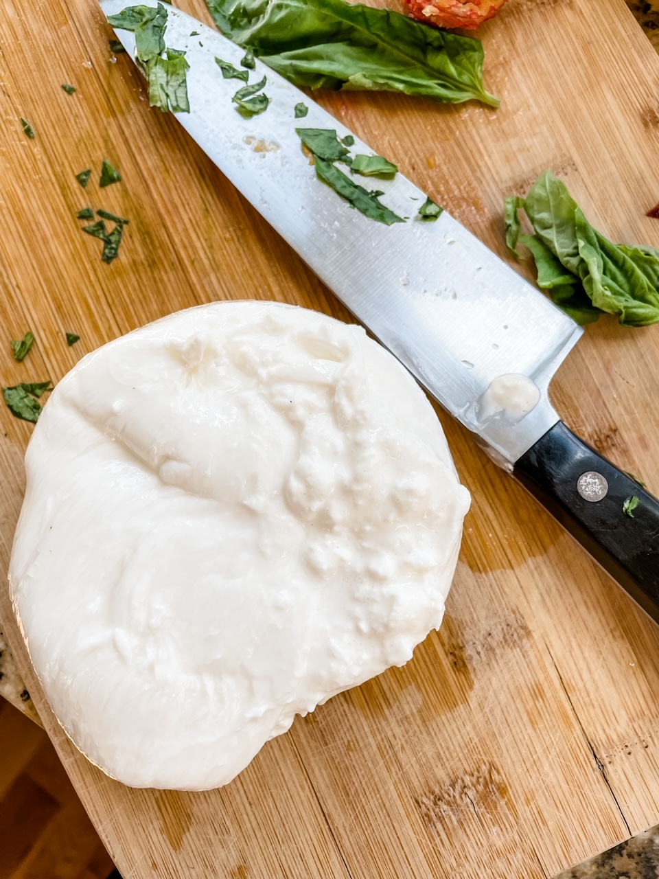 A hunk of burrata, sliced in half, next to a knife on a cutting board