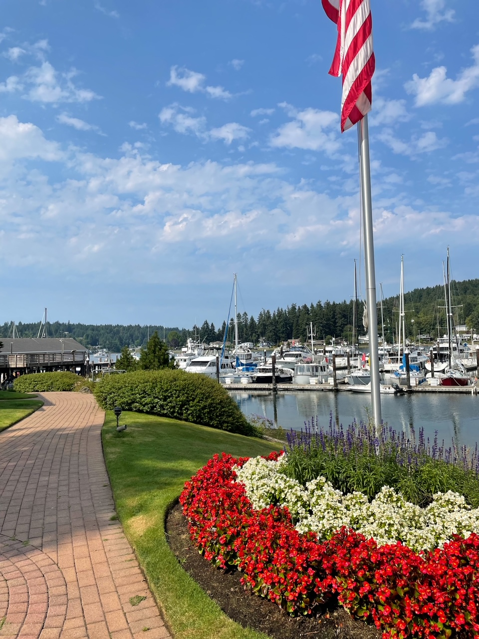 A photo of Gig Harbour, a waterfront sidewalk with landscaped flowers and boats