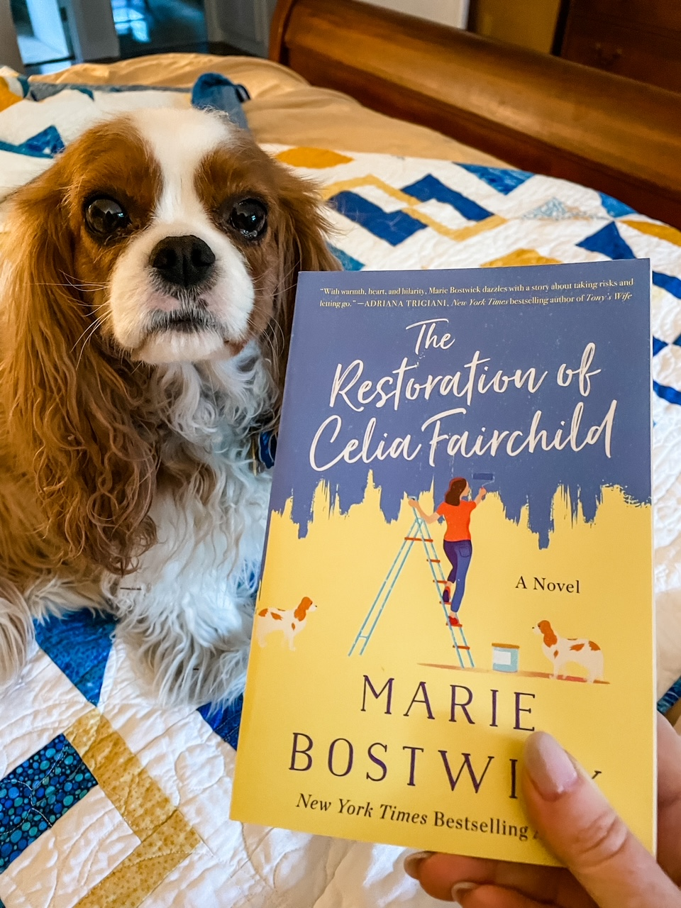 Marie holding a copy of the Restoration of Celia Fairchild above her dog.