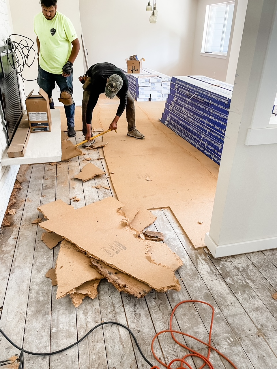 Workers tearing out the old flooring in the house