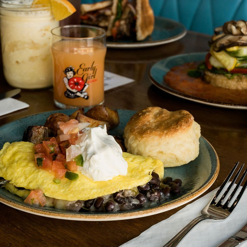 A plate with an omelet, beans, biscuit, and OJ from Early Girl Eatery