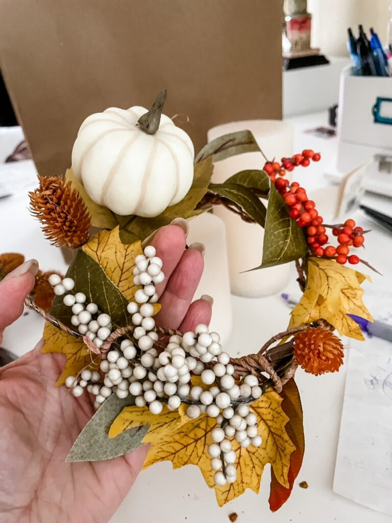 Mini pumpkins and fake berries being added to the DIY Fall Candle Wreaths