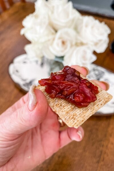A cracker being held up with some of the Easy Tomato Jam with Maple spread on it