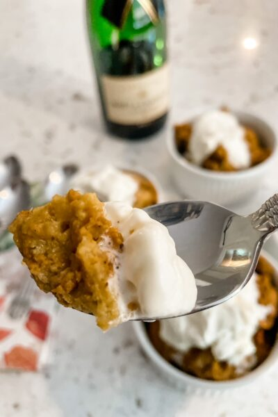 The Slow Cooker Pumpkin Bread Pudding served in three small white bowls with a spoon holding up a scoop of one