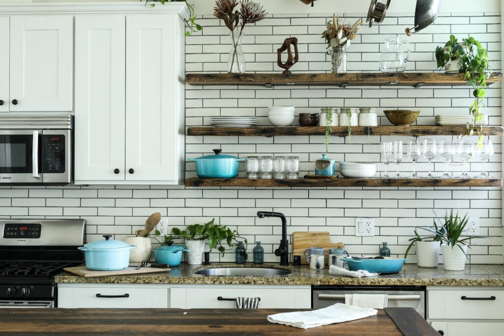 A slightly disorganized kitchen with open shelving and lots of plates and equipment