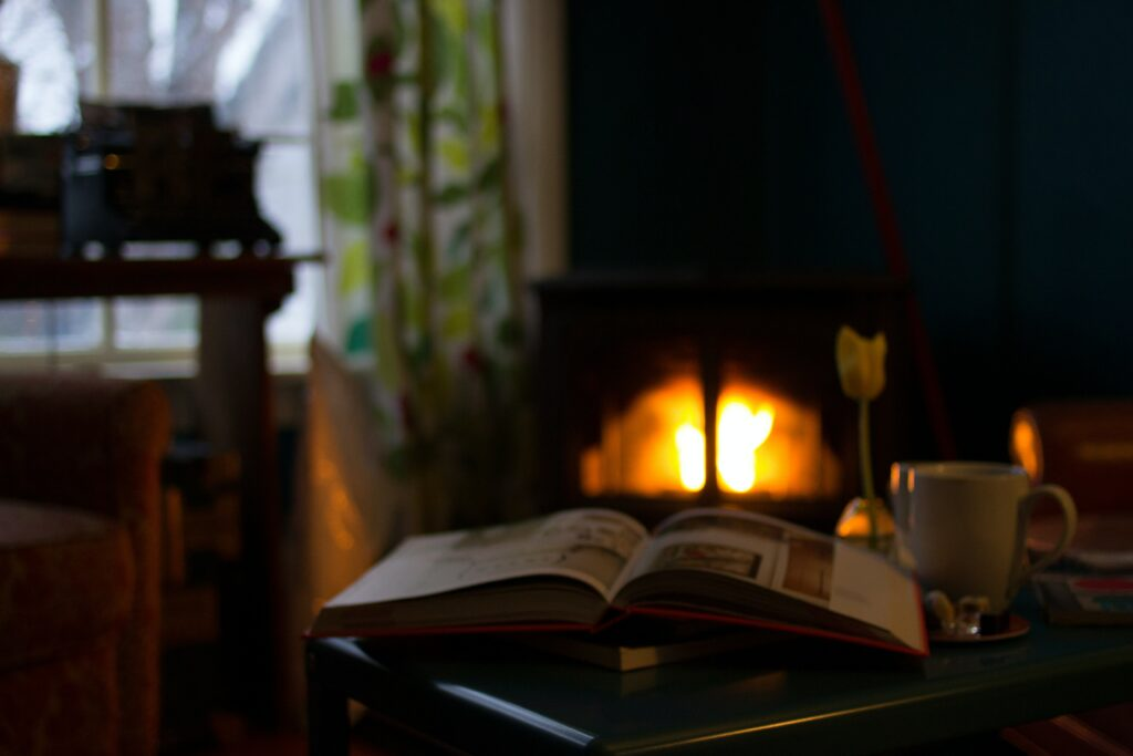 A living room with a fireplace, books, and an open window on a rainy evening