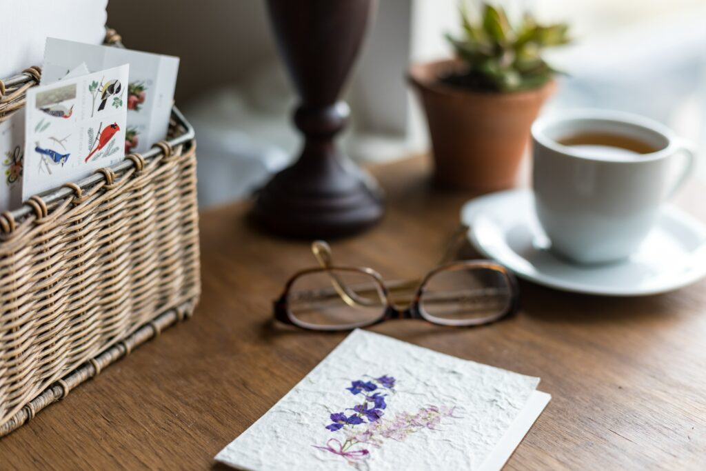 A basket of cards and a finished letter next to a pair of glasses and cup of tea