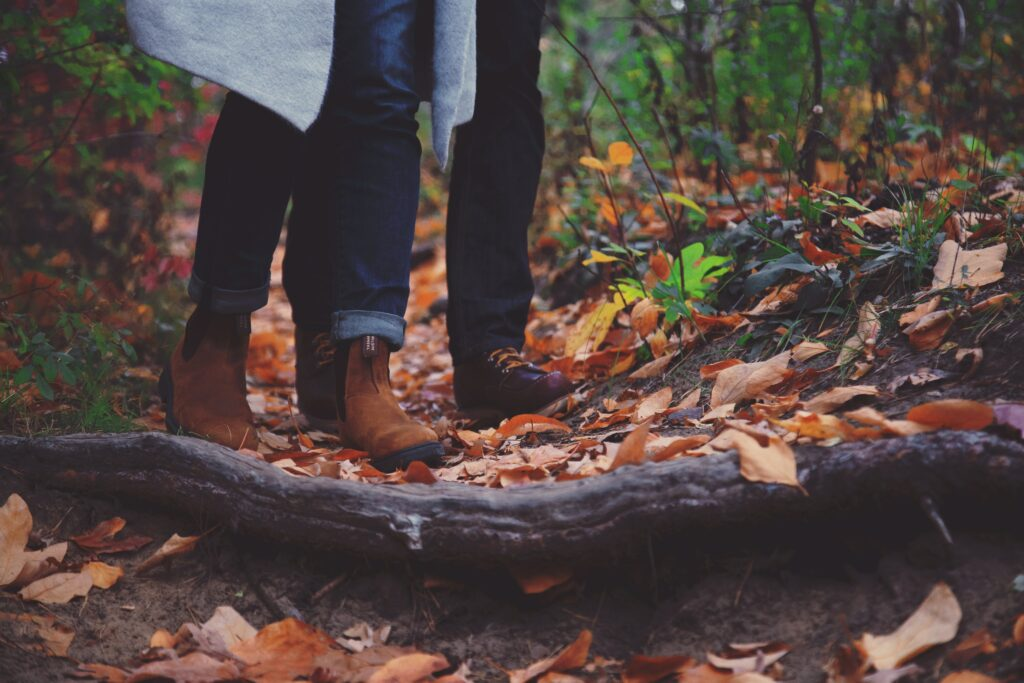 A pair of legs walking in a rainy forest path