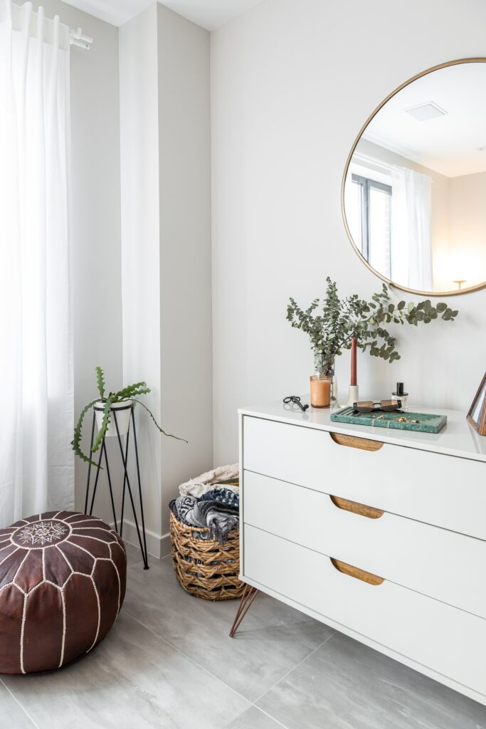 A white room with ample lighting and a dresser